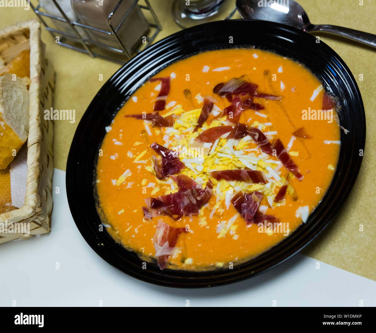 Traditional Spanish cold soup Salmorejo from tomatoes with bread, garlic and olive oil served with jamon and boiled egg - Stock Image