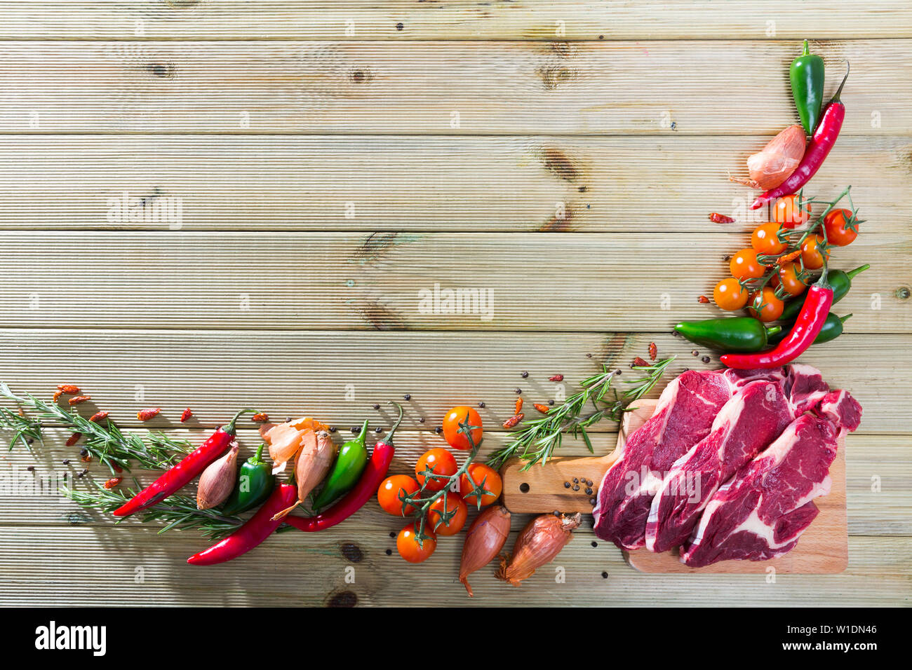 Border of food objects - sliced veal on wooden cutting board, fresh vegetables and herbs - Stock Image