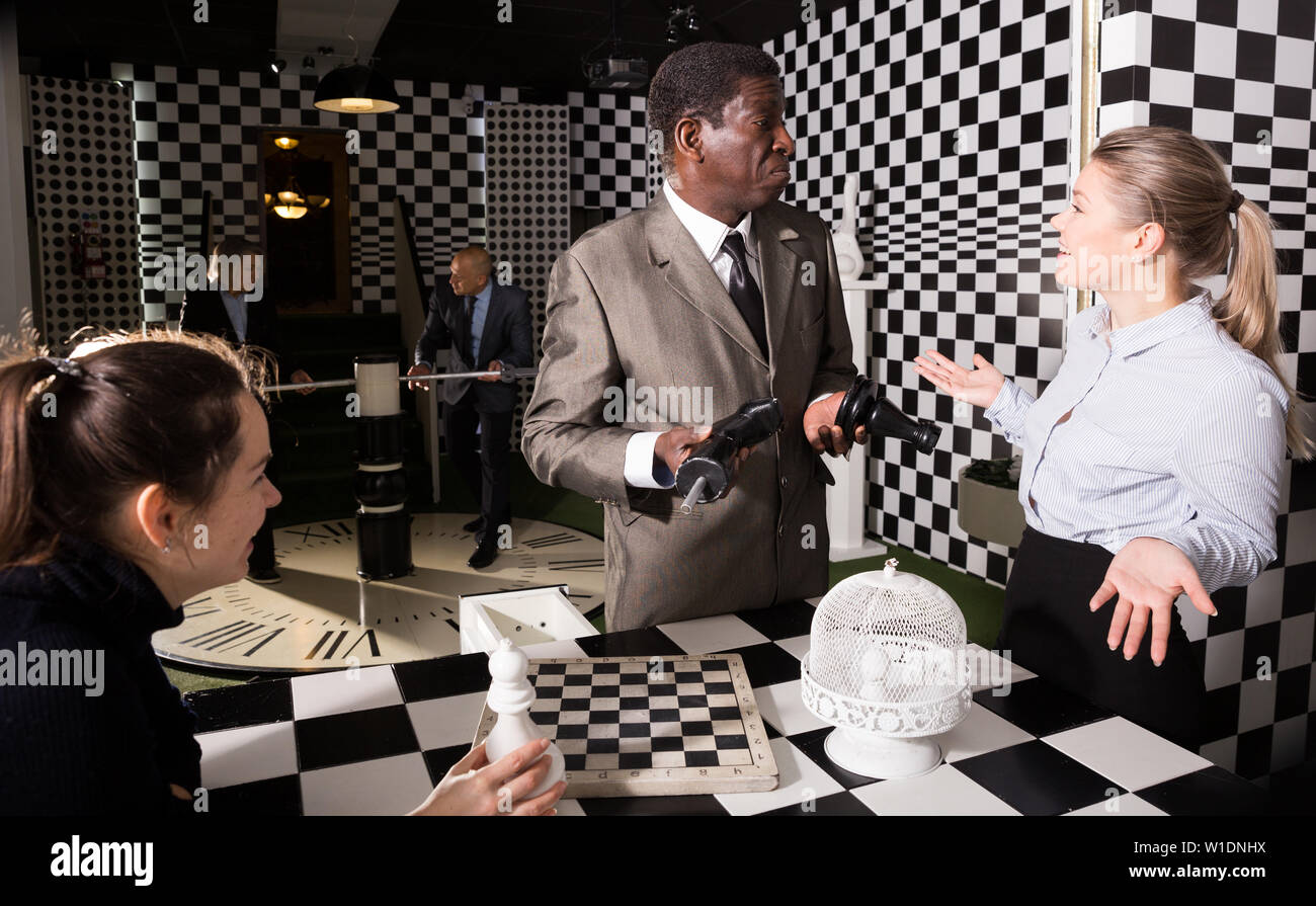 Men and women in business suits solving puzzles with chess to get out of escape room - Stock Image