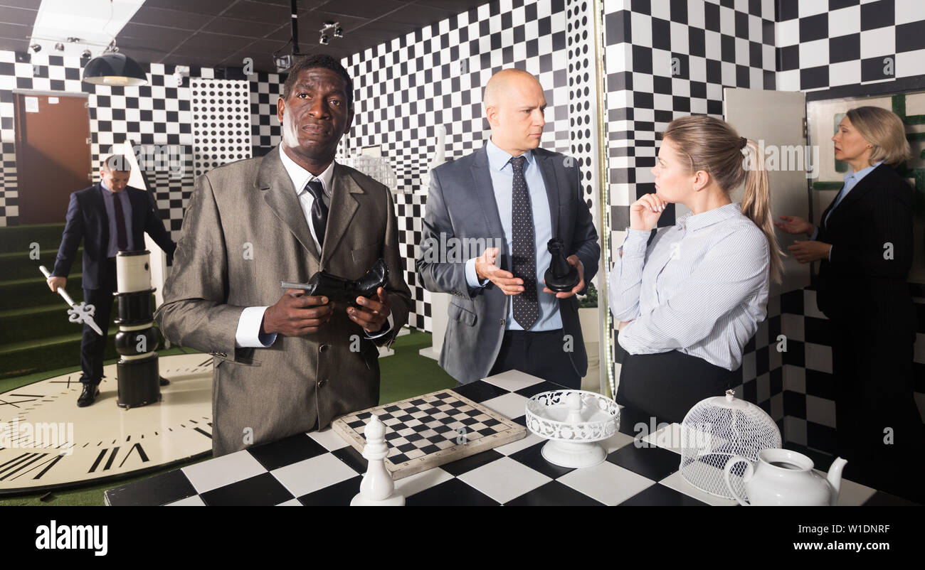Portrait of confused thinking man in business suit in escape room - Stock Image