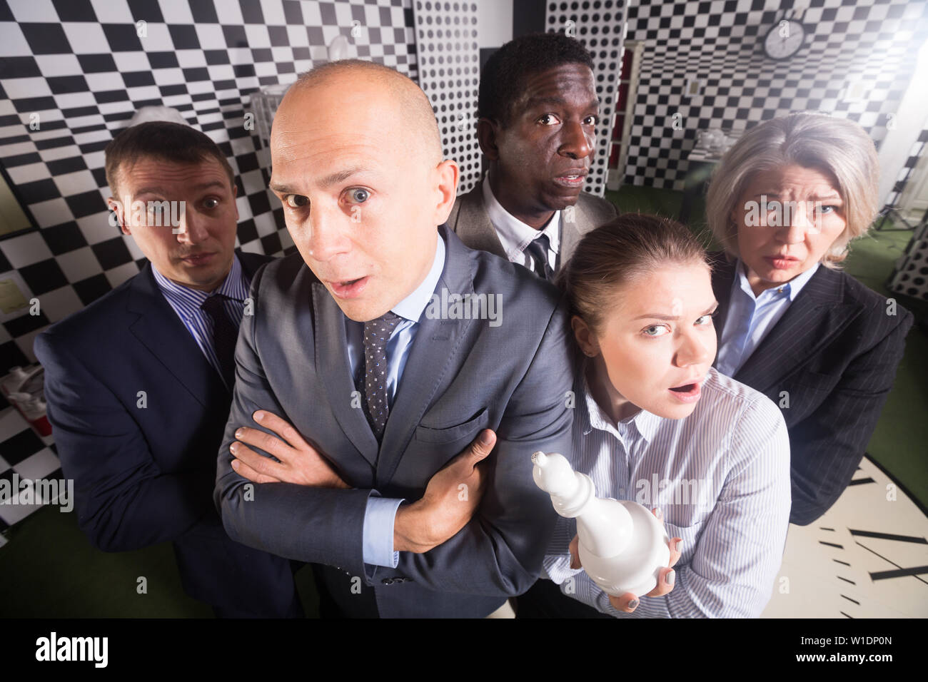 Portrait of thoughtful men and women spending time in escape room - Stock Image