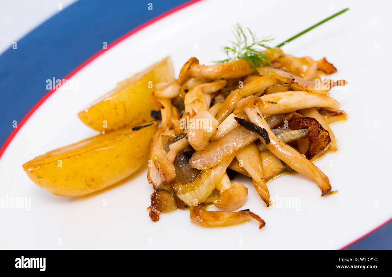 Fried oyster mushrooms served with baked potatoes and fresh greens - Stock Image