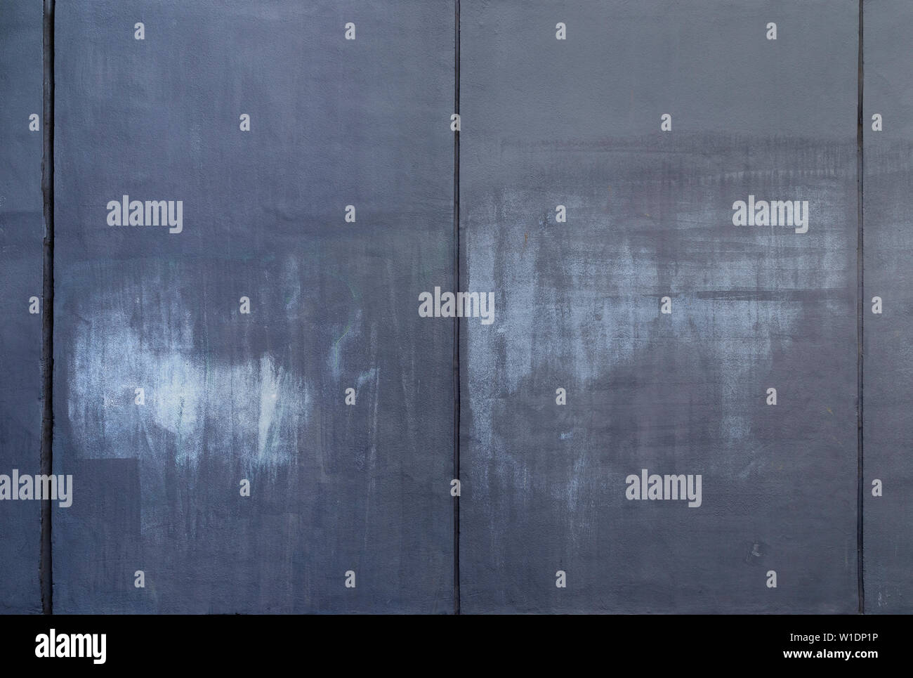 High resolution full frame background of a dark concrete wall painted in gray with lighter marks as a result of graffiti removal. Copy space. Stock Photo