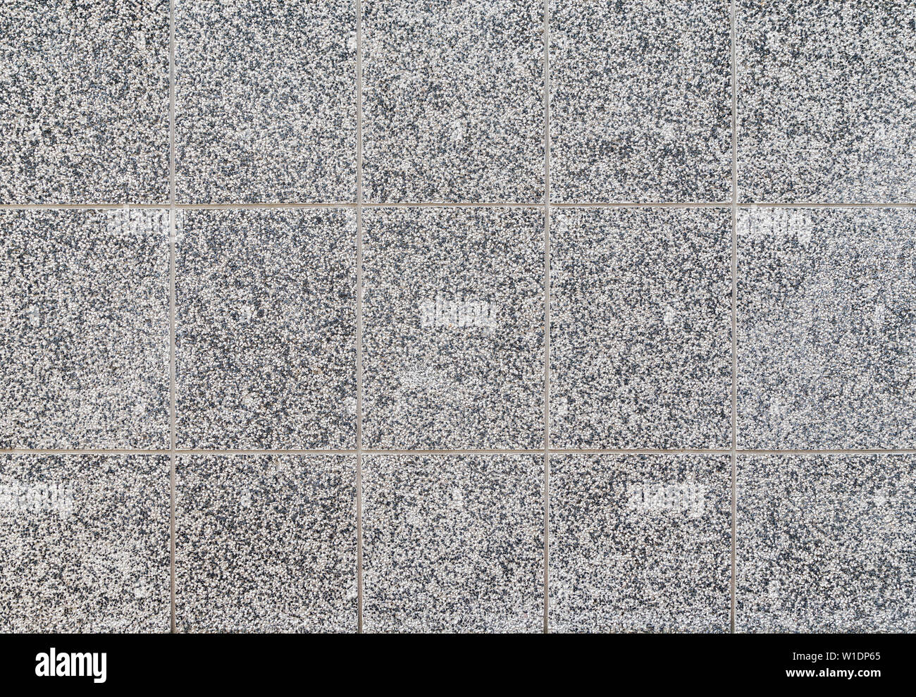 High resolution full frame textured background of a building exterior wall with small mixed black and white pebbles. Stock Photo