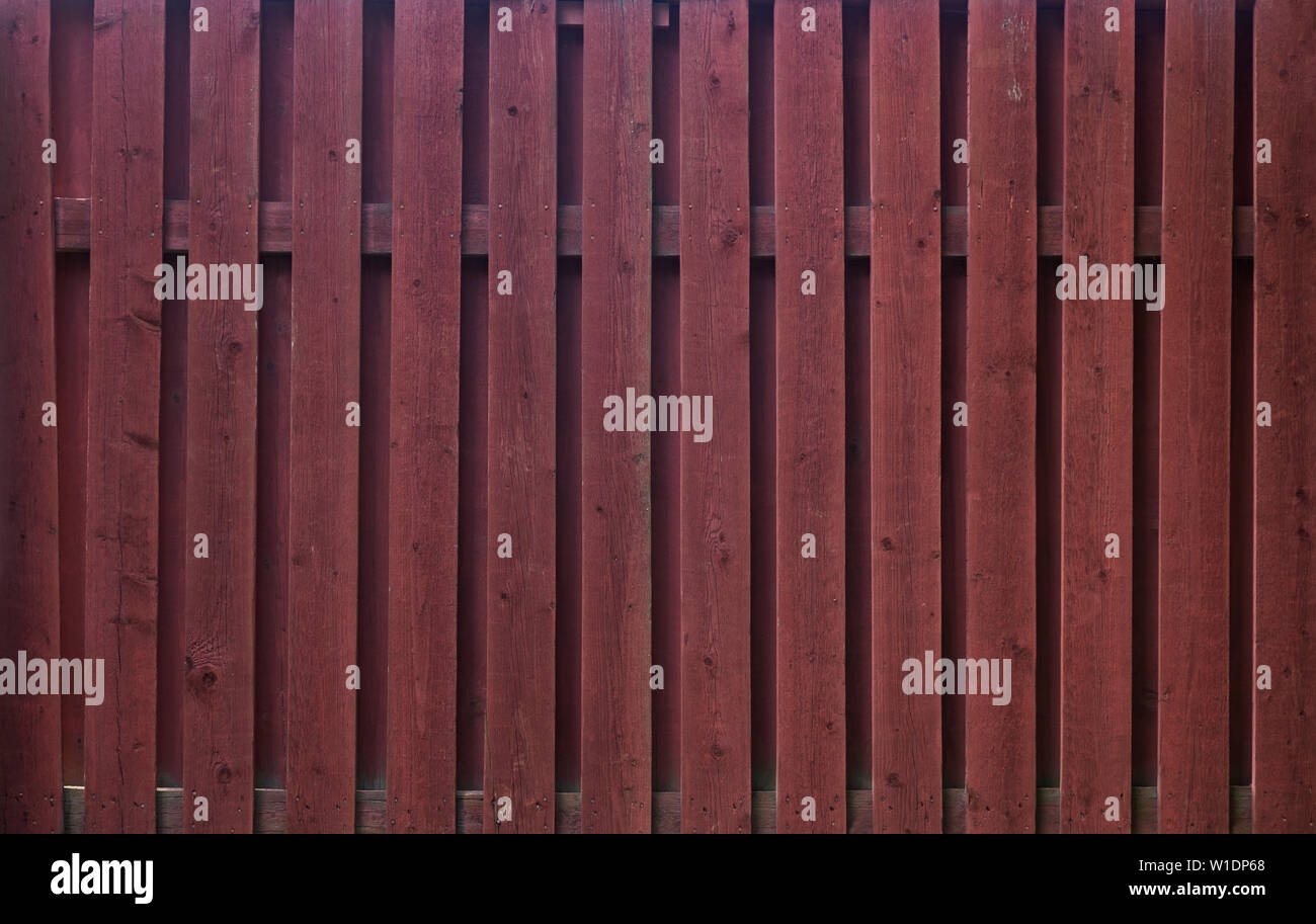 High resolution full frame background of a wooden fence painted in red. Copy space. Stock Photo