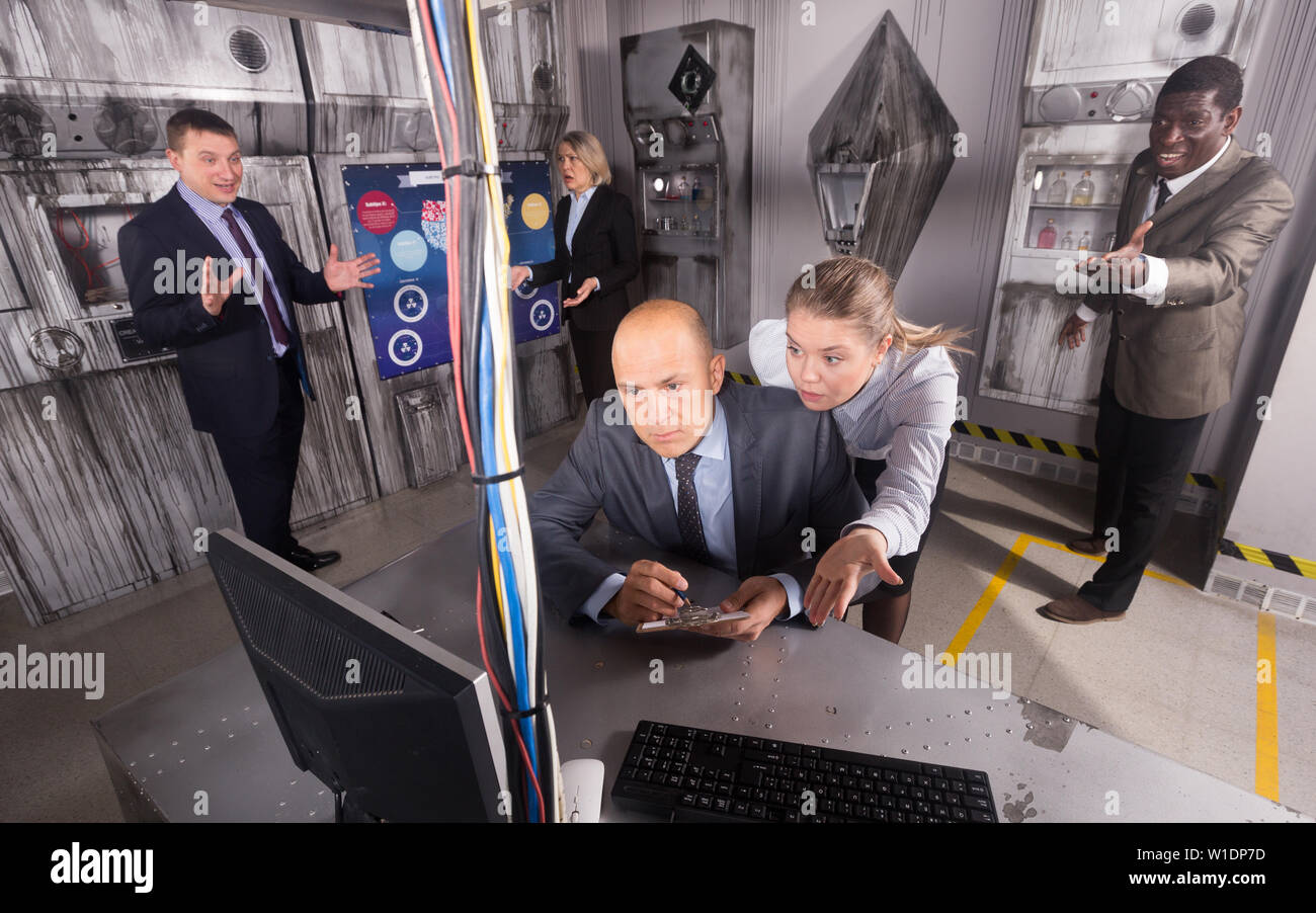 Men and women in business suits solving quests to get out of escape room - Stock Image
