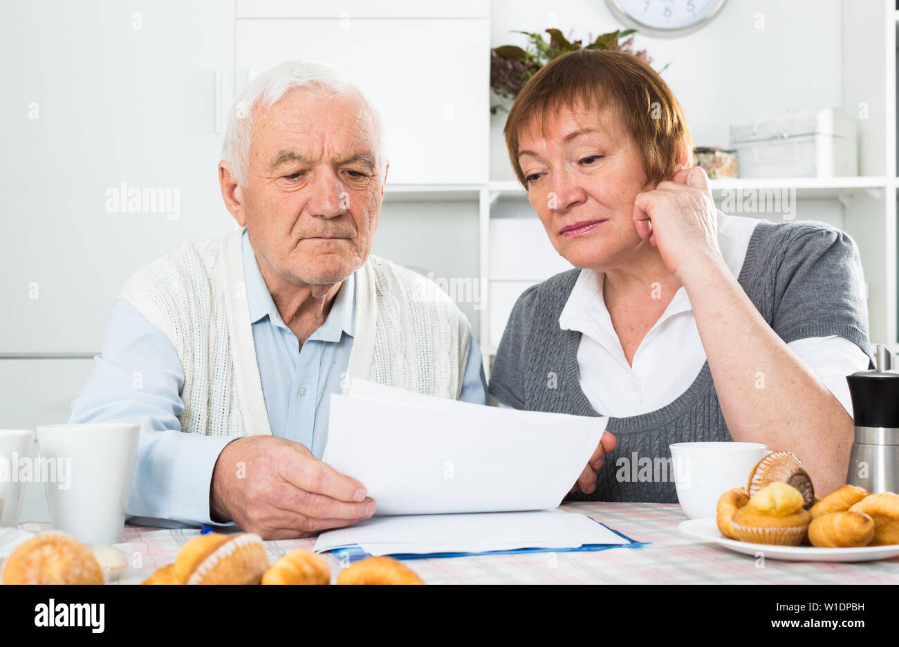 Elderly husband and wife carefully study contract before signing at home - Stock Image