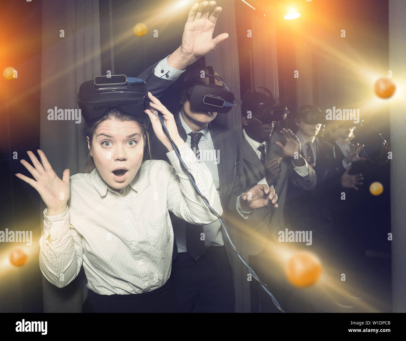 Portrait of girl and her colleagues wearing virtual reality glasses in entertainment room - Stock Image