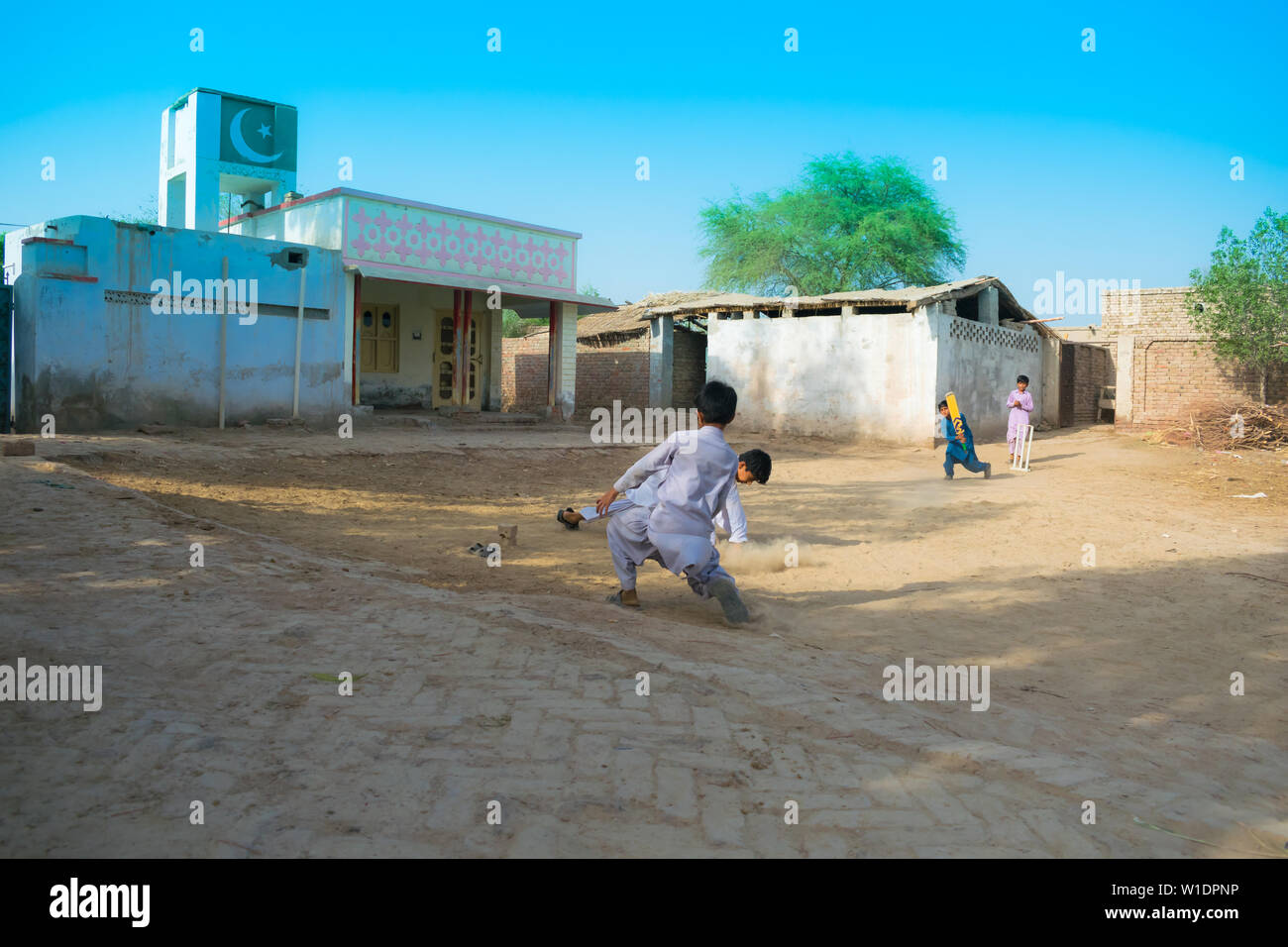 rahimyar khan,punjab,pakistan-july 1,2019:some local boys playing cricket in a village,fielder is trying to catch the ball. - Stock Image