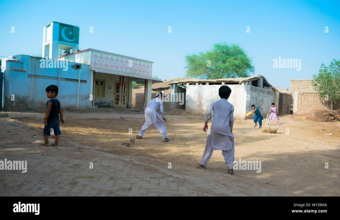 rahimyar khan,punjab,pakistan-july 1,2019:some local boys playing cricket in a village,batsman playing a shot,dust flying. Stock Photo