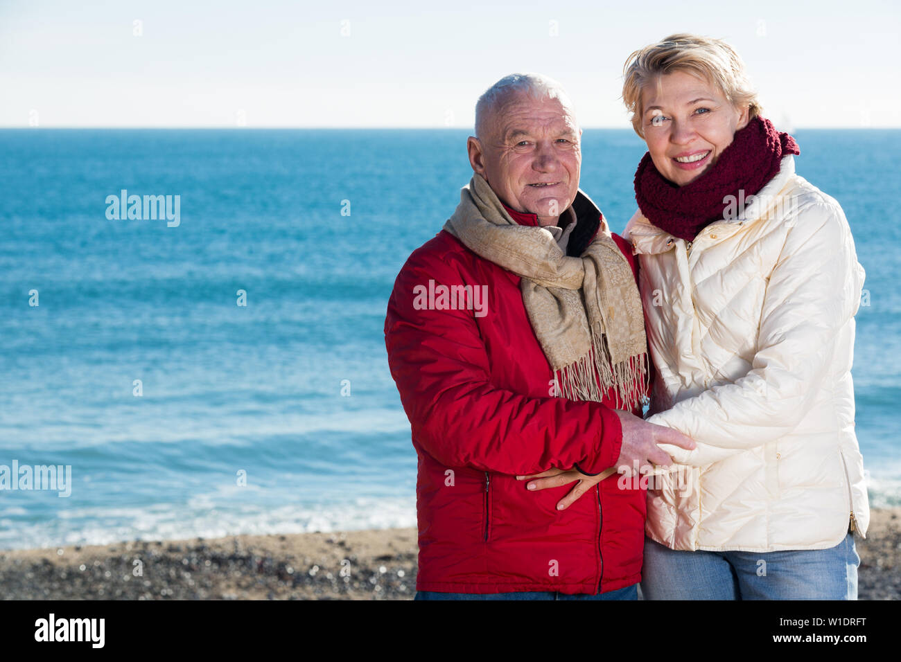 Mature man and woman walking by sea on sunny day - Stock Image