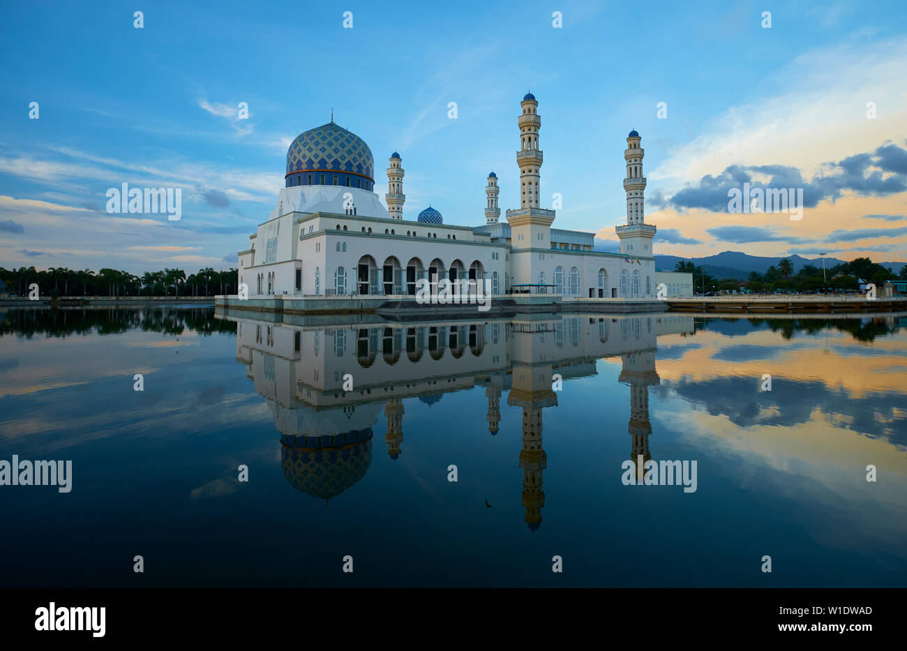 The Moorish style main city Mosque, Masjid Bandaraya, reflected at sunset in Kota Kinabalu, Borneo, Malaysia. - Stock Image