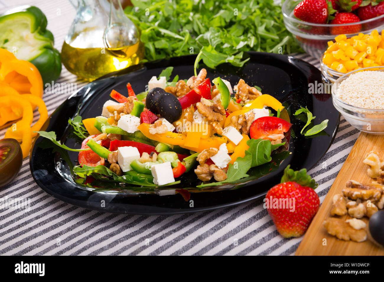 Plate with ready-made salad and its ingredients for recipe in restaurante. Stock Photo