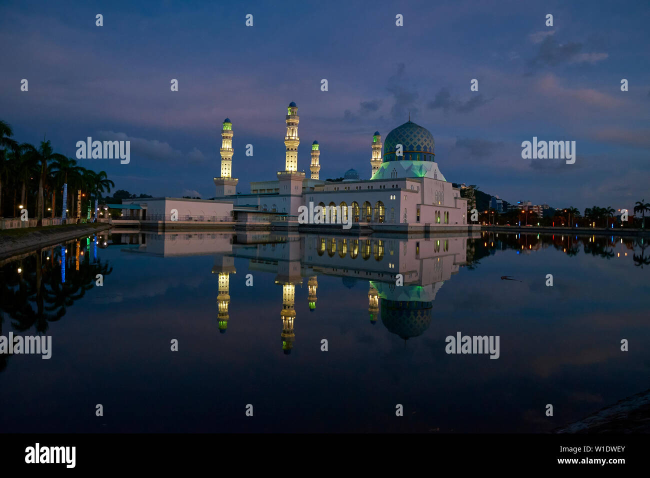 The Moorish style main city Mosque, Masjid Bandaraya, glowing at sunset in Kota Kinabalu, Borneo, Malaysia. - Stock Image