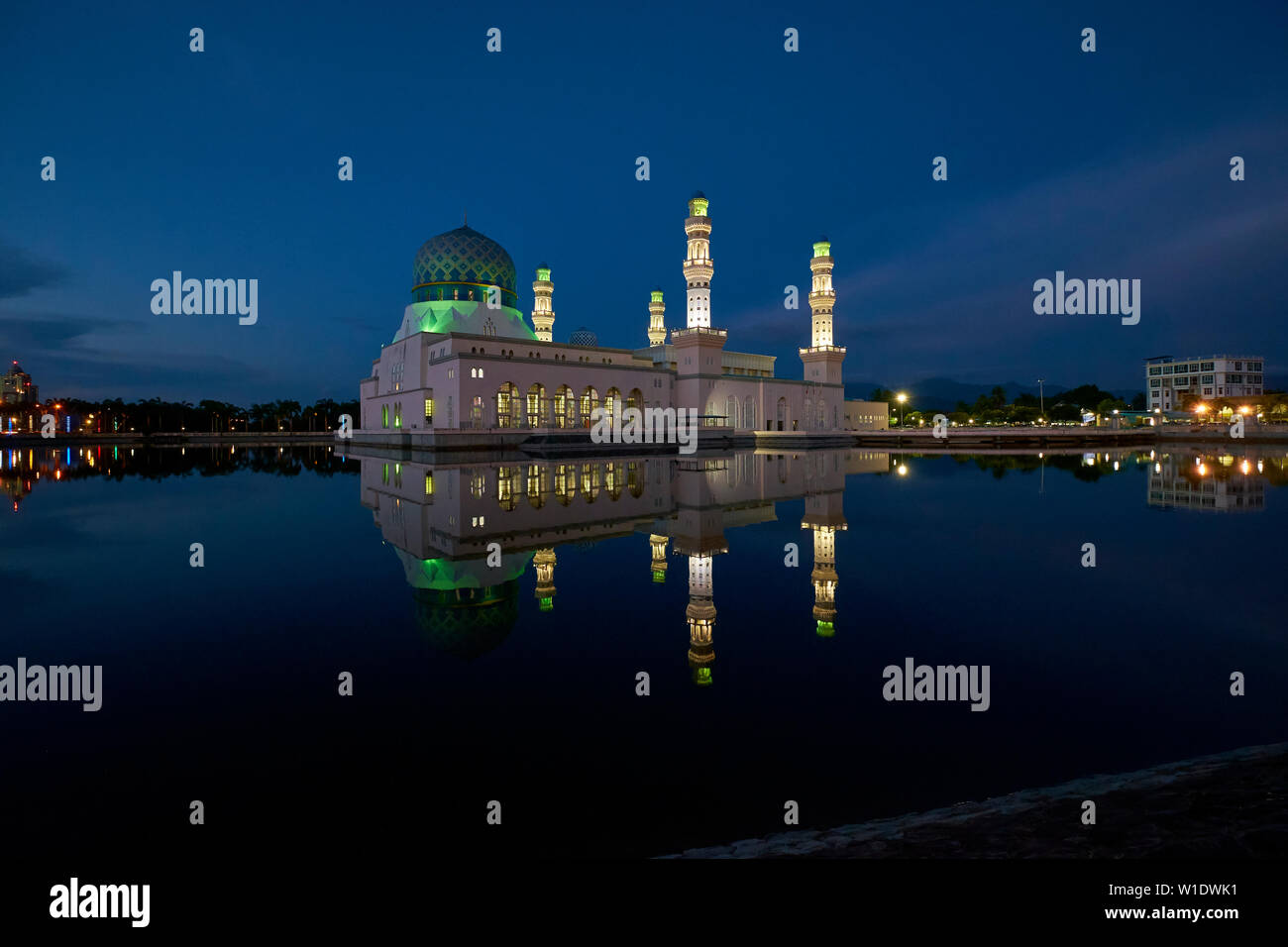 The Moorish style main city Mosque, Masjid Bandaraya, reflected at dusk in Kota Kinabalu, Borneo, Malaysia. - Stock Image