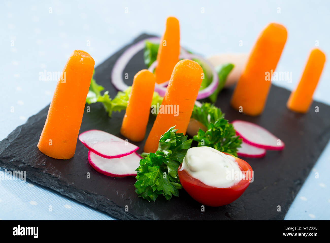 Vegetarian lunch - raw vegetables and greens on black plate - Stock Image