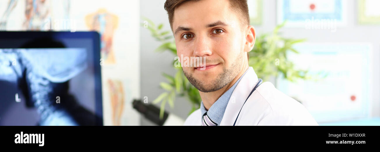 Smiling male doctor working with compute in his office Stock Photo