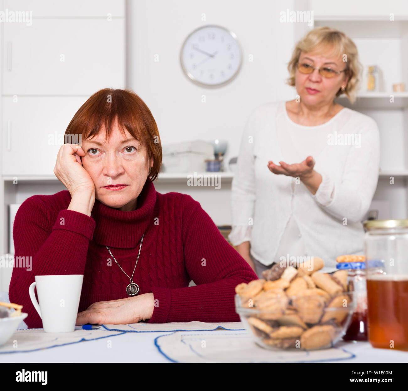 Two offended elderly women squabbling at home - Stock Image