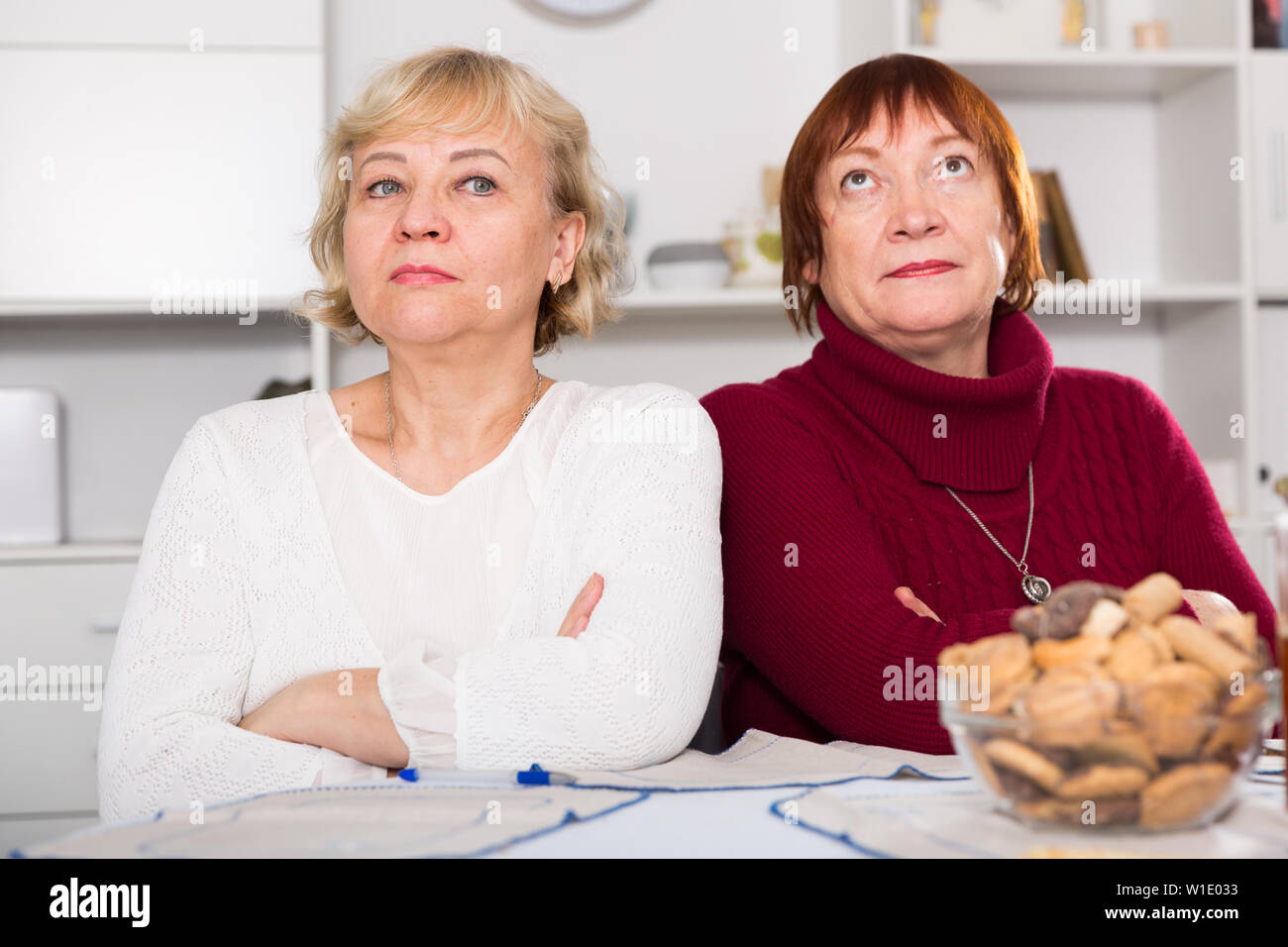 Pensioners females quarreling at kitchen near food at the table - Stock Image
