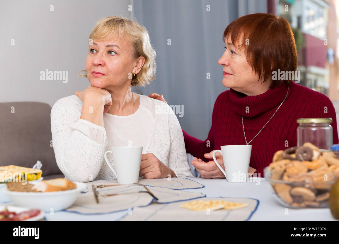 Mature lady trying to calm her female friend and apologize after quarrel - Stock Image