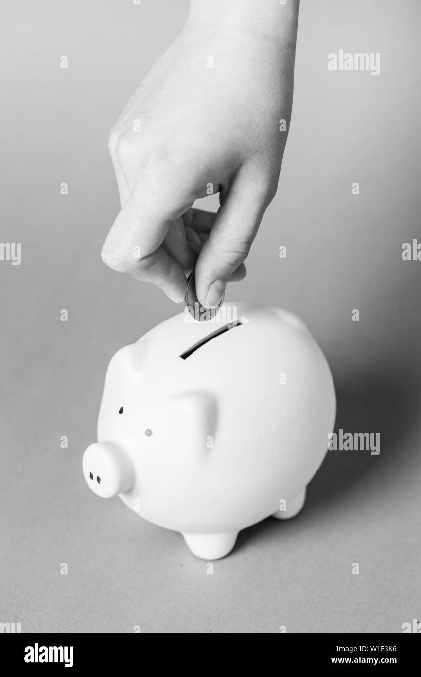 Inserting a coin into a piggy bank - Stock Image