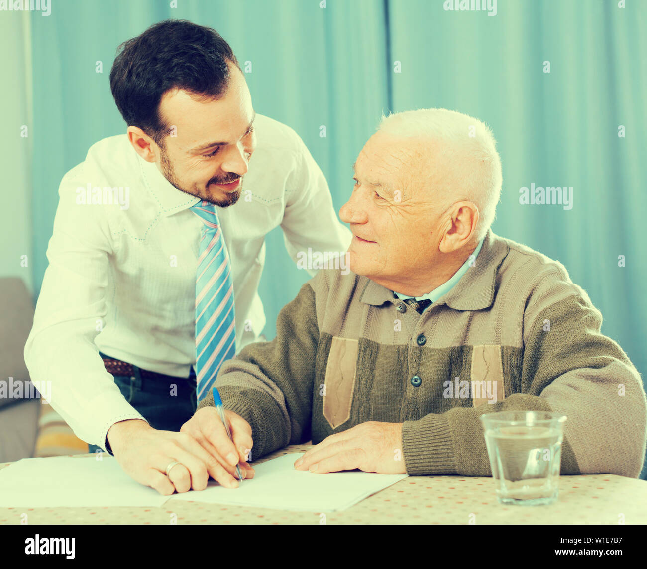 Senior man preparing agreement papers with social worker at home - Stock Image
