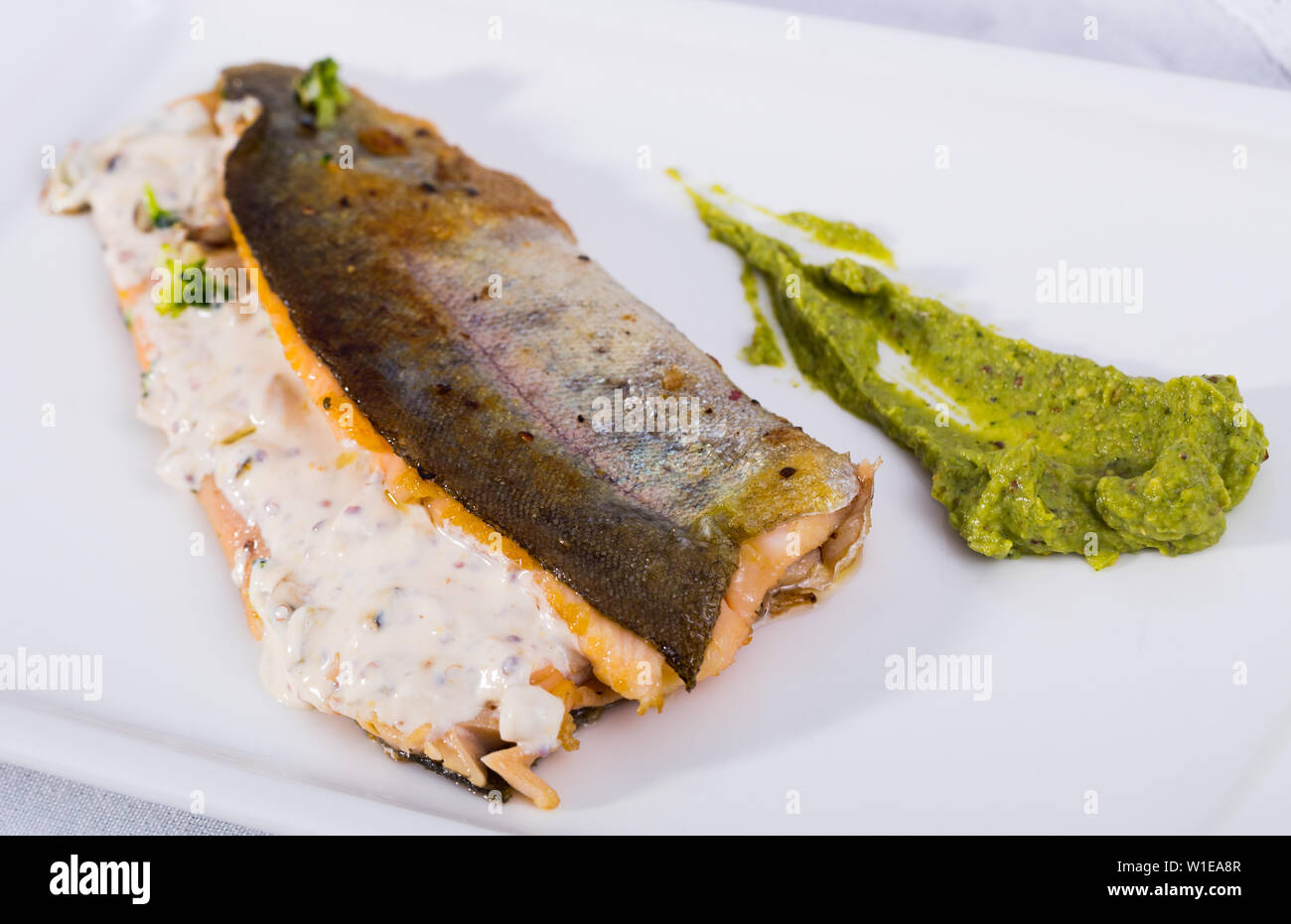 Baked trout fillets with vegetable garnish from pureed broccoli with tartare sauce on white dish - Stock Image
