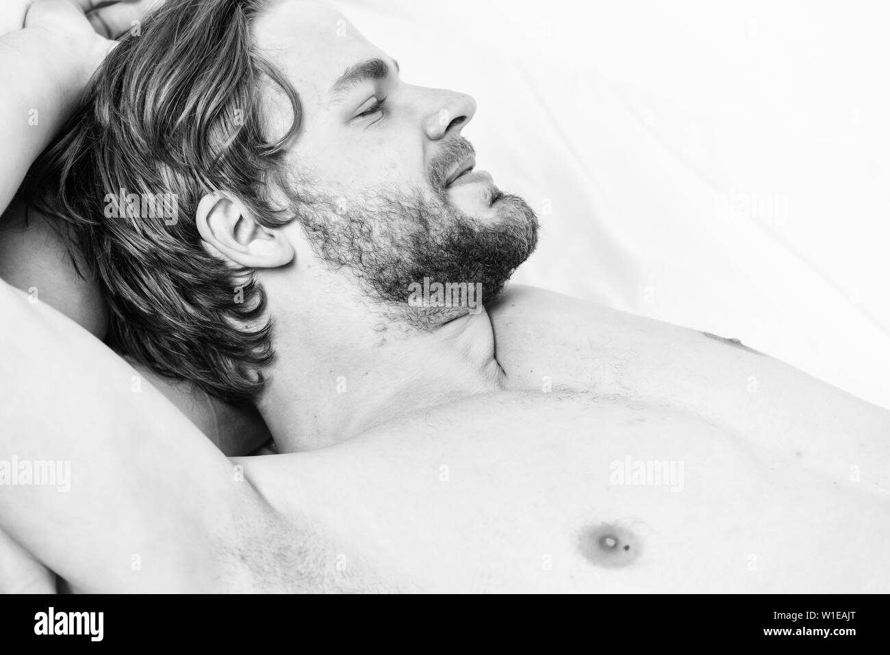 A young man waking up in bed and stretching his arms. Close up of feet in a bed under white blanket. Wake up in the morning - Stock Image