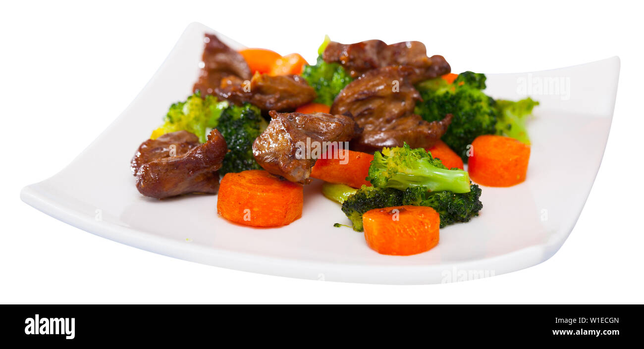 Portion of fried chicken hearts with garnish of boiled vegetables - Stock Image