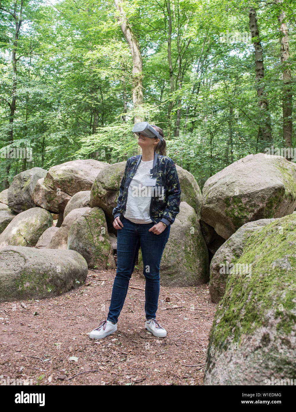Westerkappeln, Germany. 02nd July, 2019. Kerstin Schierhold, Stone Age expert of the Landschaftsverband Westfalen-Lippe (LWL) tests the animation of the Great Sloopsteene near Westerkappeln in the district of Steinfurt with virtual reality glasses. The stones are the best preserved grave in Westphalia. Visitors can now see how the tomb once looked from the inside and outside with technical help, virtual reality glasses or on their own smartphone. Credit: Caroline Seidel/dpa/Alamy Live News Stock Photo