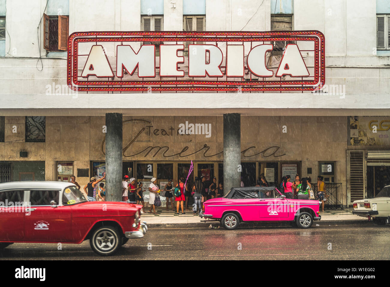 Pink and red vintage cars outside Teatro America in rain, La Habana (Havana), Cuba, West Indies, Caribbean, Central America - Stock Image