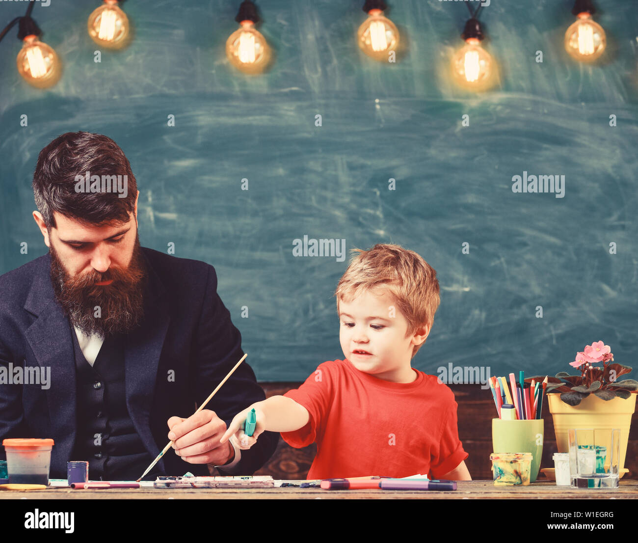Teacher with beard, father teaches little son to draw in classroom, chalkboard on background. Child and teacher on busy face painting, drawing. Art lesson concept. Talented artist spend time with son. Stock Photo