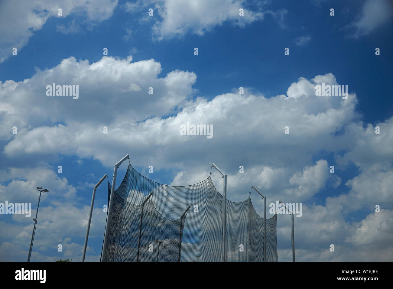 Throwing cage at an athletics track in bright summer sunshine - Stock Image