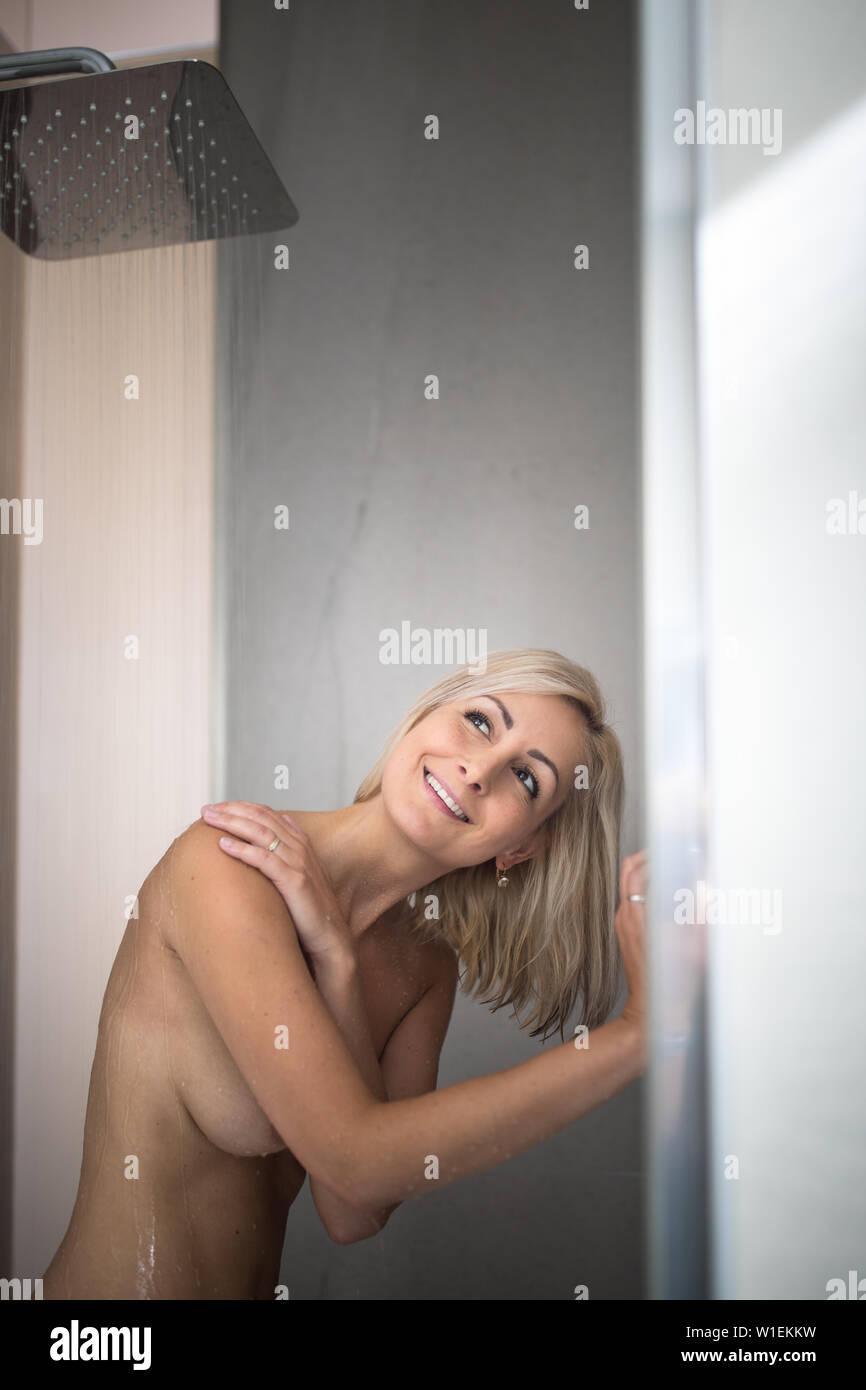Woman Taking A Long Hot Shower In A Modern Design Bathroom Stock