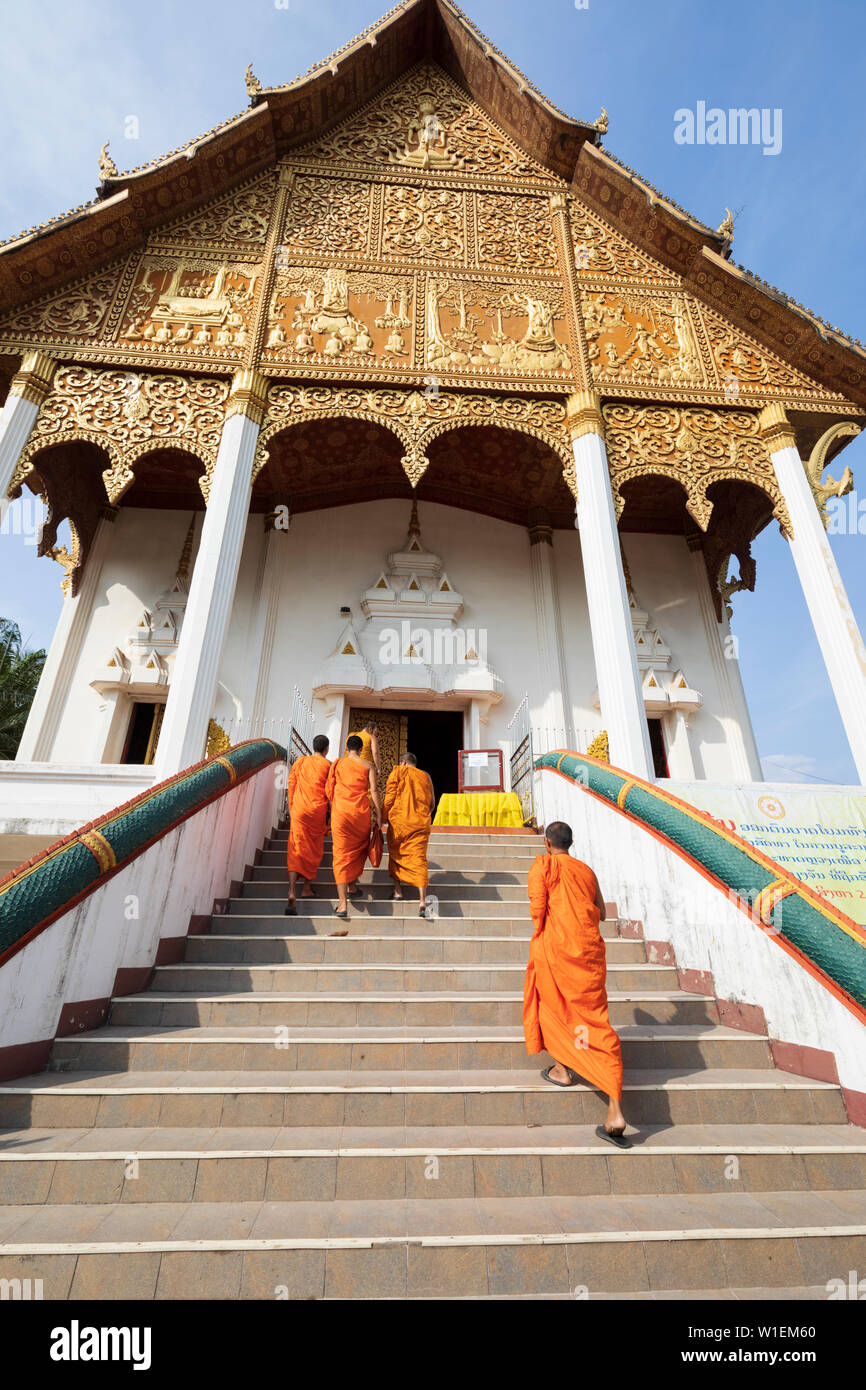 Buddhist monks climbing stairs to a temple at the Pha That Luang, Vientiane, Laos, Indochina, Southeast Asia, Asia Stock Photo