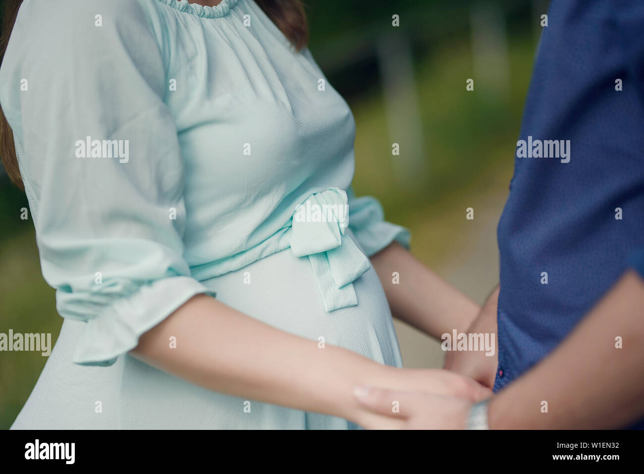 Cropped shot of handsome Caucasian couple holding hands with focus on the pregnant woman's beautiful round tummy, concept for happy family expecting Stock Photo