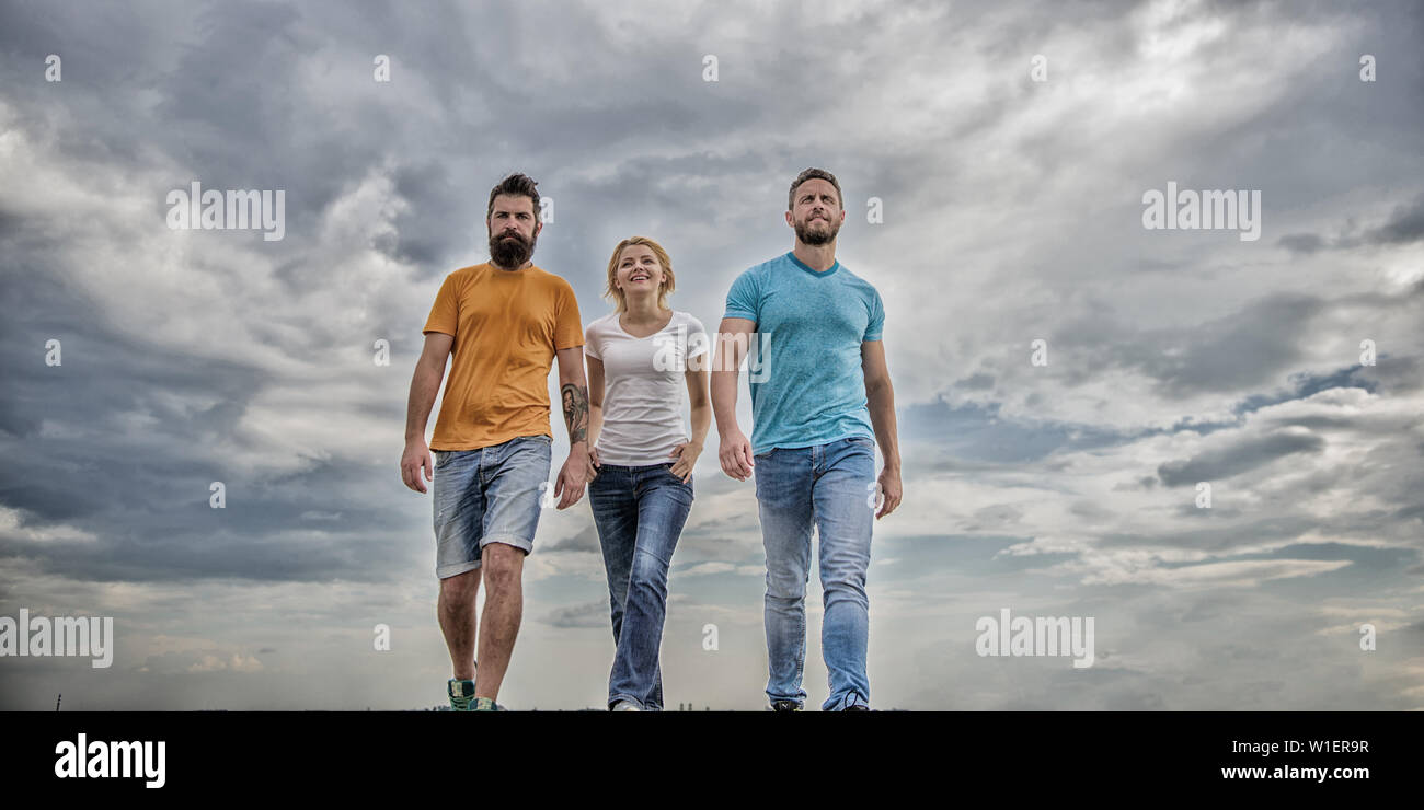 Friendship tested for years. United threesome true friends. Men and woman walks dramatic cloudy sky background. True friendship grow with destiny obstacles. United group purposefully moves forward. - Stock Image