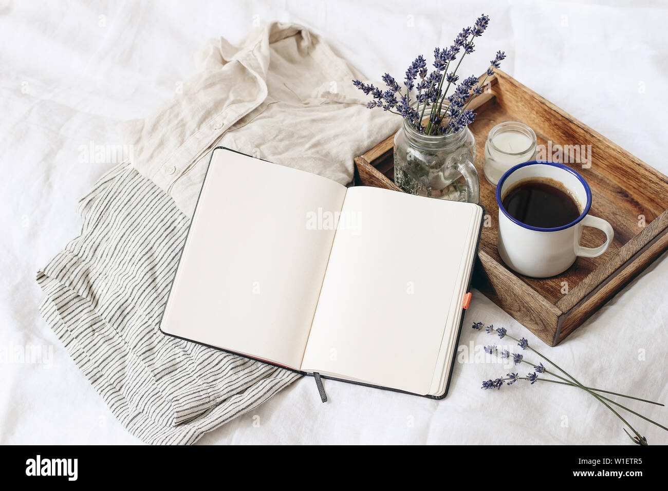 French summer still life. Feminine lifestyle composition. Cup of coffee, lavender flowers bouquet, candle on wooden tray. Linen shirt nad trousers on Stock Photo