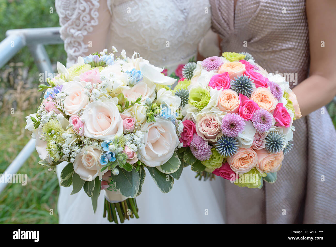 Bride And Maid Of Honor Or Bridesmaid Holding Large Colorful And Sophisticated Wedding Bouquets Caucasian Young Women Holding Flower Arrangements Stock Photo Alamy