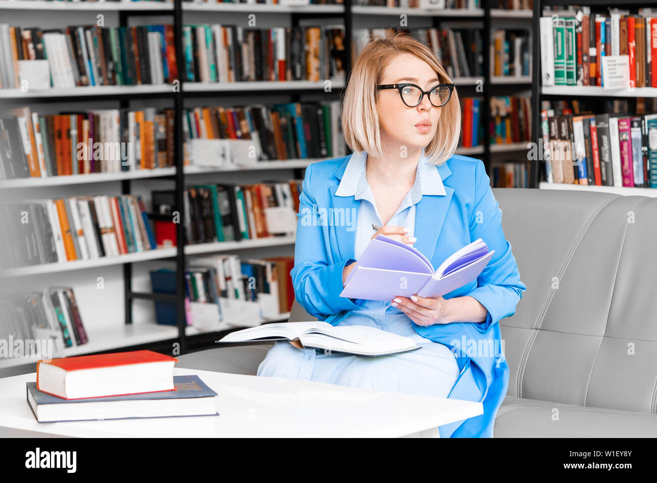 Young pensive attractive woman in formal attire makes some notes in notepad at library. Stock Photo