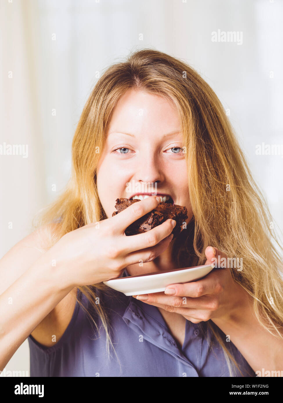 Photo of a beautiful blond woman in her early thirties with log blond hair eating a large piece of brownie or cake. - Stock Image