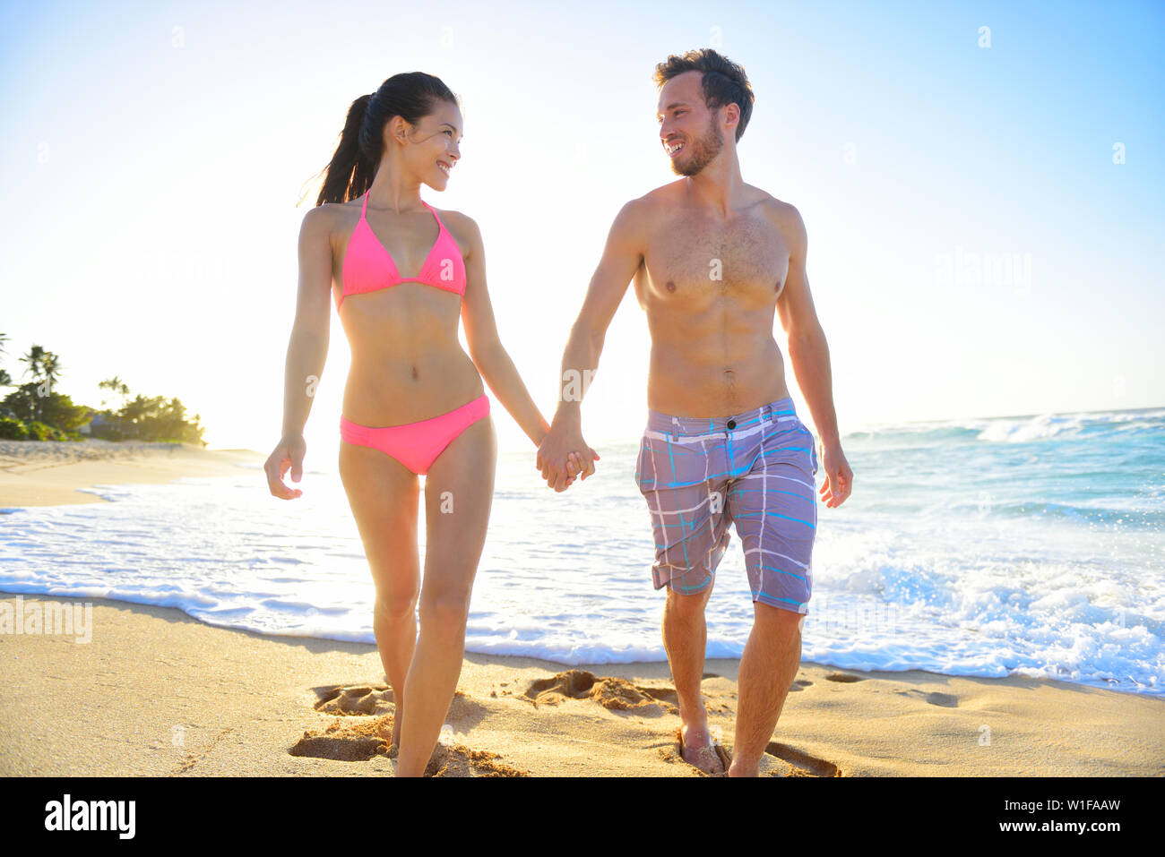Young interracial romantic beautiful couple walking in beach sand holding hands smiling happily. Relaxed mixed race couple enjoying romance on vacation travel. Asian woman, Caucasian man. - Stock Image