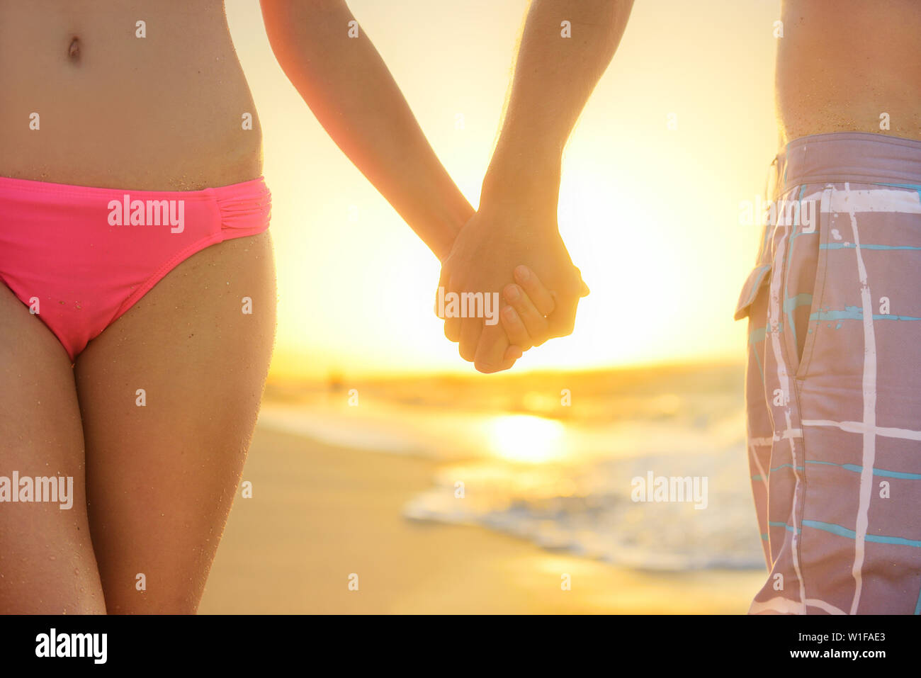 eeb43e4a27b Lovers or romantic young couple holding hands in romance on beautiful  sunset at beach. Young