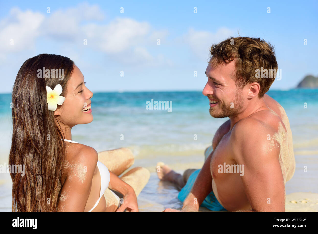 Vacation couple relaxing on beach tanning laughing talking together. Portrait of two young adults mixed race asian caucasian having fun during travel holidays. - Stock Image