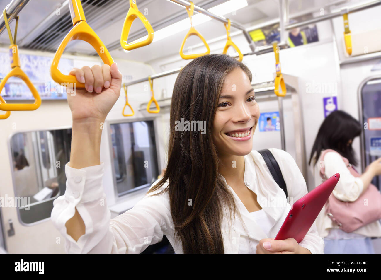 Subway commuter woman on Japanese public transport in Tokyo, Japan. Tourist using Japan's capital city metro system to commute. Portrait of happy asian lady holding handhold inside the wagon. Stock Photo