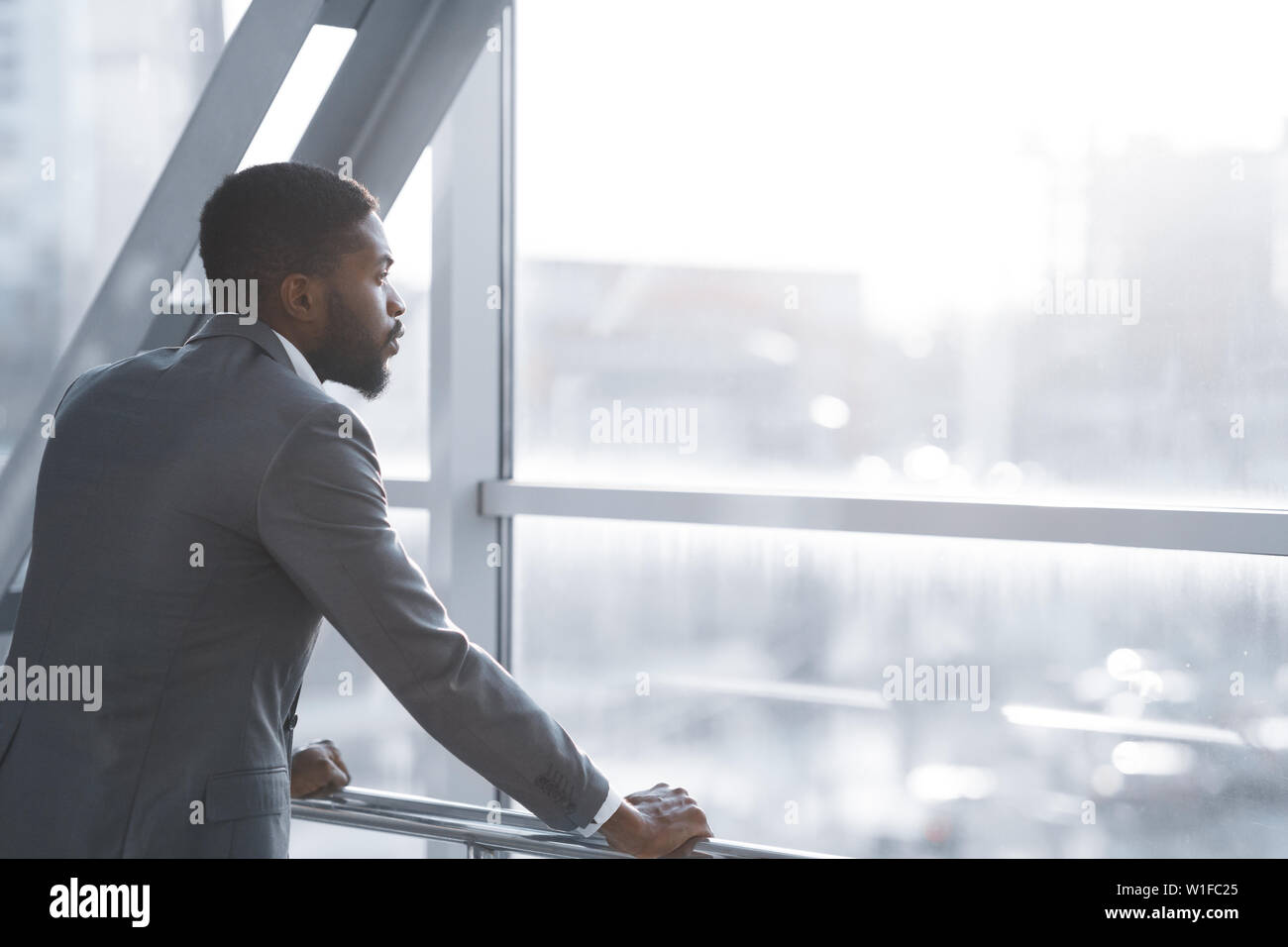 Wait for Flight. Afro Businessman Looking Through Window - Stock Image