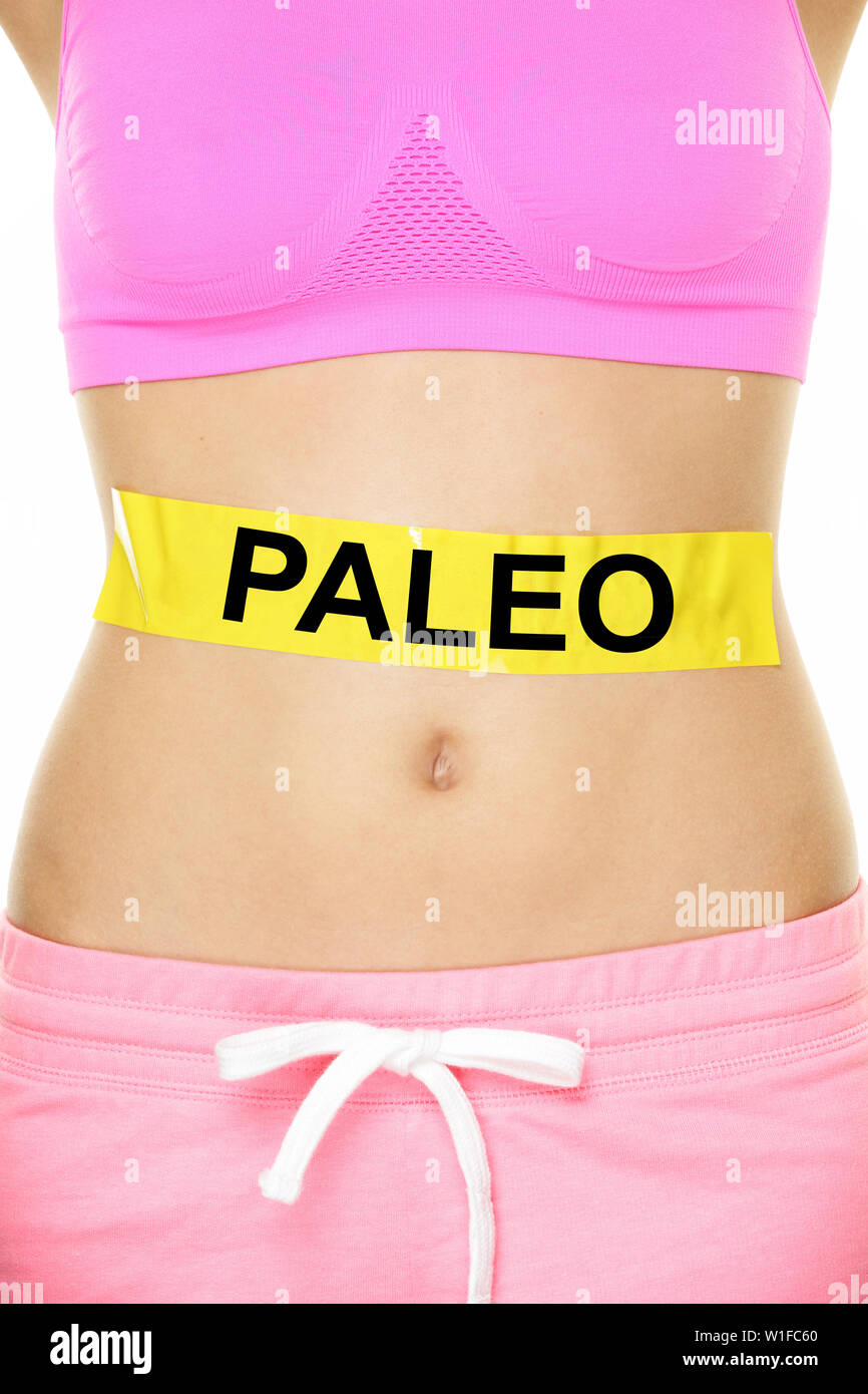 Paleo diet concept - closeup of woman's stomach to show eating concept. New trend in nutrition based on hunter gatherer consumption of proteins. Yellow label as warning or caution applied on body. Stock Photo