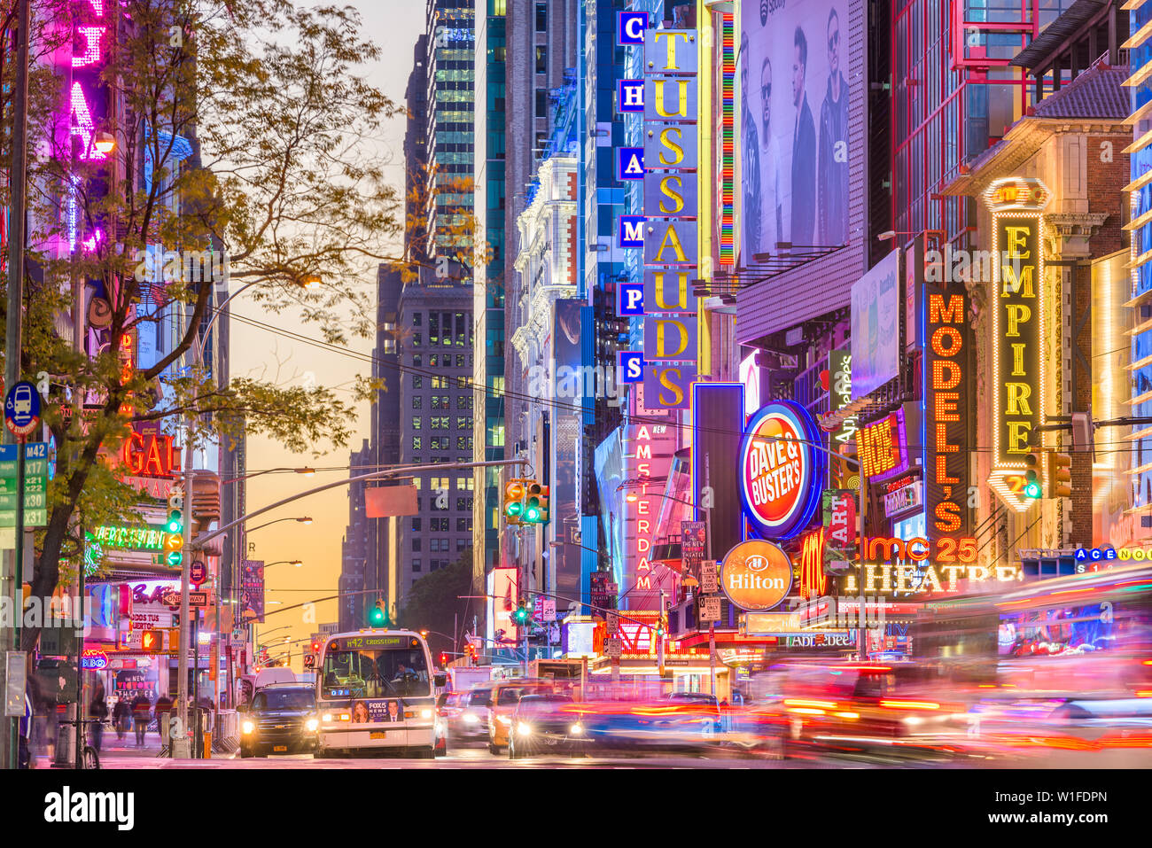 NEW YORK CITY - NOVEMBER 14, 2016: Traffic moves below the illuminated signs of 42nd Street. The landmark street is home to numerous theaters, stores, Stock Photo