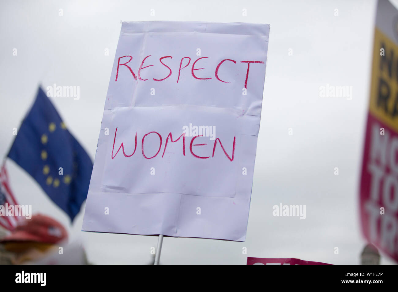A protestor holds a political banner with respect women message - Stock Image
