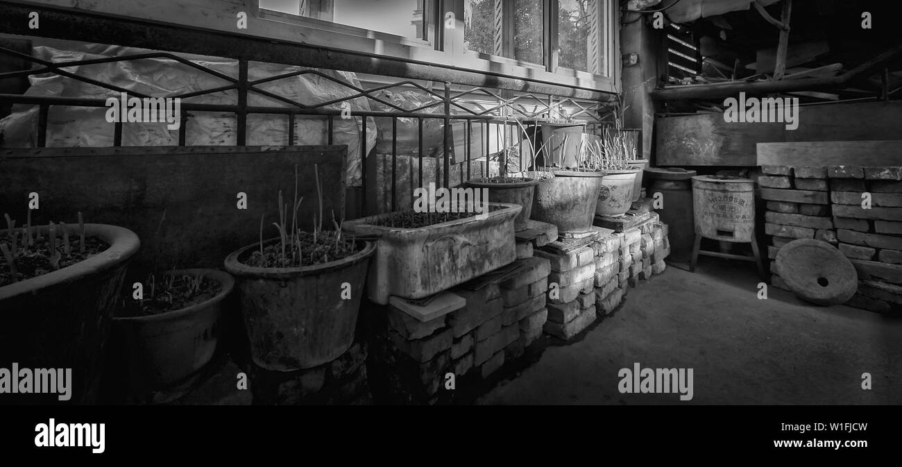 It's the typical scene of Chinese old buildings' stairway. People planting vegetables here, storing abandoned grocery here,  cooking here...etc. Altho - Stock Image